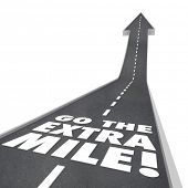 The words or saying Go the Extra Mile on a road with arrow going upward to illustrate improvement, i