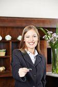 Smilinge female receptionist at hotel offering a key card