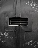 Black door with a peephole protected by iron bars