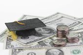 stock photo of copper coins  - Mortar board and stack of quarters on American one dollar bills and one hundred dollar bills close up - JPG