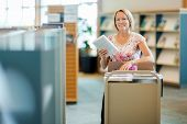 foto of librarian  - Portrait of smiling female librarian with trolley of books in library - JPG