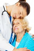 Young female doctor embracing senior woman isolated over white background