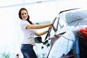 Pretty woman standing near car at car center. Choosing a car