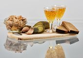 Two short glasses of whisky and snack on a board