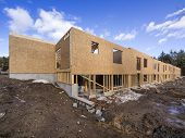 picture of 2x4  - New framing house construction with no roof and two by fours exposed - JPG