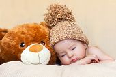 Little baby boy, sleeping with teddy bear