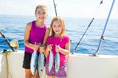 stock photo of catching fish  - Happy tuna fisherwomen kid girls on boat with fishes trolling catch - JPG