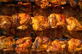 Roasted chicken in a row turning at industrial roaster