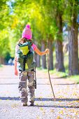 hiking kid girl with walking stick and backpack rear view at autumn track and camouflage pants