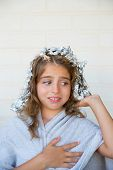 Funny kid girl scared about his dye hair with foil blue eyes