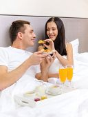 hotel, travel, relationships and happiness concept - smiling couple having breakfast in bed in hotel
