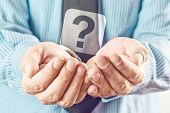 image of begging  - Businessman holding question mark - JPG