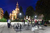 SARAJEVO, BOSNIA AND HERZEGOVINA - AUGUST 13, 2012: Men play chess on the street with large chess pi