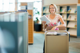 image of librarian  - Portrait of smiling female librarian with trolley of books in library - JPG