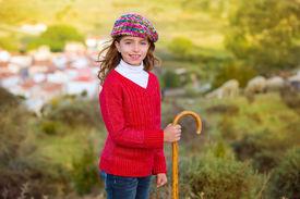 stock photo of shepherdess  - Kid girl shepherdess smiling with wooden baston in Spain village - JPG