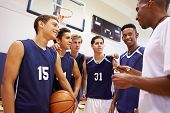 stock photo of black american  - Male High School Basketball Team Having Team Talk With Coach - JPG