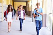 High School Students Walking In Hallway Using Mobile Phone