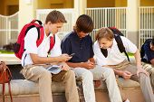 Male High School Students Using Mobile Phones On School Campus