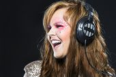 A woman sings as she listens to music on headphones