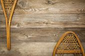 vintage Huron snowshoes against grained wood planks with a copy space