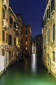 Canal with medieval palaces at night in Venice