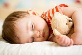 stock photo of innocence  - infant baby boy sleeping with plush toy - JPG