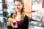 Woman presenting muffins and cupcakes in bakery or pastry shop