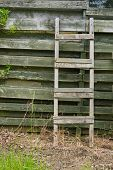 Weathered Wooden Ladder Leaning On Wooden Slats