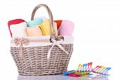 Colorful towels in basket, pins and liquid for washing, isolated on white