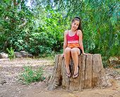 Teenager Girl Sitting On A Tree Trunk