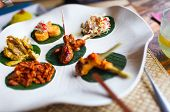 Variety of traditional Bali appetizers including cjicken satay, chicken curry, beef and vegetables