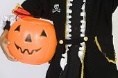 Midsection of a boy in Halloween outfit holding pumpkin bucket isolated over white background