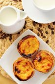 a jar and a cup with milk, and some pasteis de nata typical Portuguese egg tart pastries, on a set t