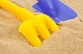 a blue toy shovel and a yellow toy rake on the sand of a beach or a sandpit