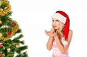 woman in santa claus hat blows on open hands