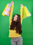 Shopping happy young woman holding colored bags over green studio background.