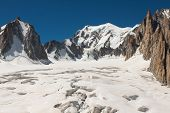 stock photo of crevasse  - Massif de mont Blanc on the border of France and Italy. In the foreground the ice field and crevasses of the Valley Blanche