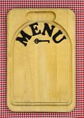 Menu sign with iron key on wood cutting board with red checkered (gingham) background
