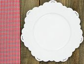 Sign with red checkered (gingham) tablecloth with empty white plate on rustic table