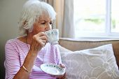 Mature woman sitting inside sipping her tea
