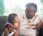 Portrait Indian family at home. Grandparent and grandchild eating cake. Asian people living lifestyl