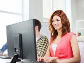 education, technology, school and people concept - smiling female student in computer class at school