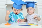Two little kids in blue graduation hats paint colors at table