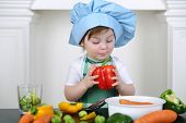 Little girl in kitchen apron and cap with large red pepper