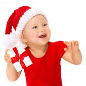 Closeup portrait of happy smiling child with Christmas gift isolated on white background, wearing red Santa hat for Xmas celebration