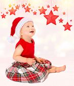 Cute happy Santa girl sitting on the floor and looking on beautiful hanging red stars toys, isolated on white background, Christmas celebration concept