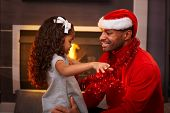 Black father in santa hat and little daughter hugging at home at christmas time.