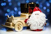 pic of christmas claus  - Santa Claus and old vintage wooden automobile with gift box on christmas lights background. Main focus of image on Santa Claus and selective on turned left wood car with gift box