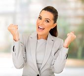 excited businesswoman waving fists in office