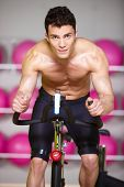Close up Topless Handsome Muscular Man Spinning a Bike at the Gym While Looking at the Camera.